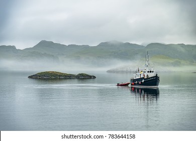 Alone boat driving through in the foggy sea in the Highlands of Scotland