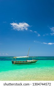 alone boat with white roof in emerald water under blue sky with little cloud in Zanzibar in Tanzania