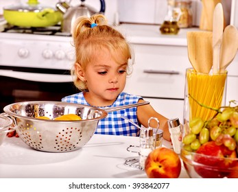 Alone child with rolling-pin dough at home kitchen. Child's cooking.