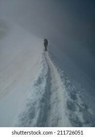 Alone climber in fog on a snow ridge