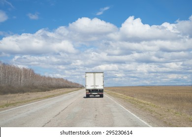 Alone Dirty Truck driving on clear spring asphalt  road against blue sky with white clouds, empty field with dry grass and forest along highway Back view car Idea symbol of logistics