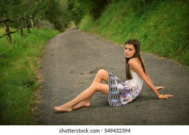 alone girl dreaming sitting on the road  in summertime rural place