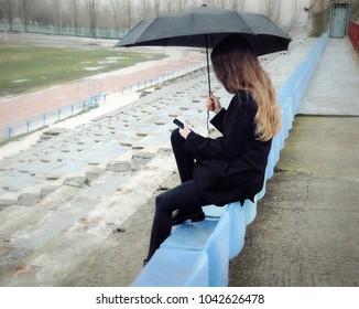 Alone girl with umbrella and smartphone sitting on the bench on desert stadium. Rain.