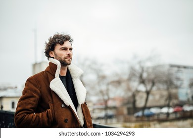 alone handsome man with beard and winter or autumn coat walking alone outside next to a river and thinking about something