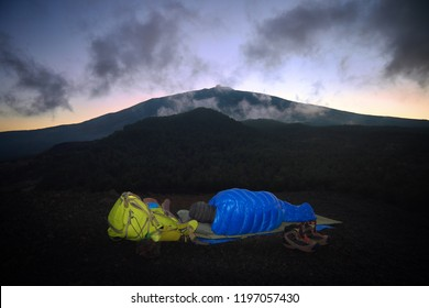 alone hiker is sleeping in blue bag on volcanic ashes in Etna Park, Sicily