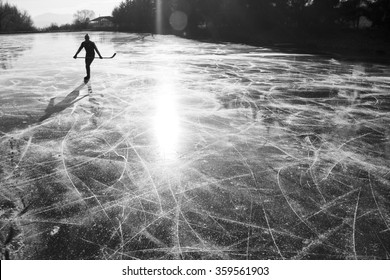 alone hockey player on frozen ice during ice skating on natural ice in rural environment