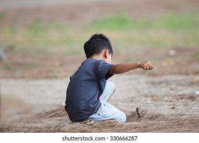 Alone kid playing on sand in the park