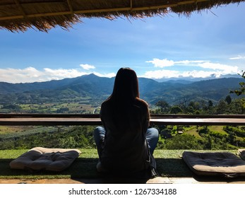 Alone lady sit on pillow and looking mountain view