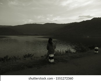Alone and lonely girl sitting on the kilometer stone looking on sunrise at country road.  Waiting and depress concept.