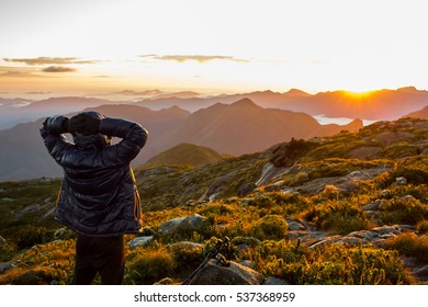 Alone man with down jacket relaxing and watching the sunrise at the mountains