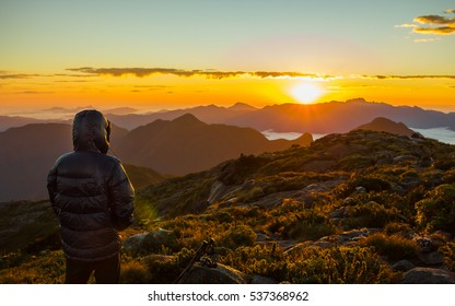 Alone man with down jacket watching the sunrise at the mountains