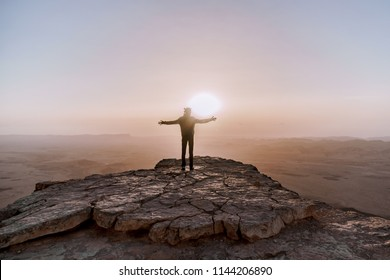 Alone man in israel negev desert admires the view of sunrise. Young male person stands on the edge of the cliff of makhtesh ramon park. Beautiful horizon landscape
