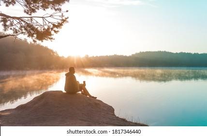 Allein der Mensch meditiert und entspannt auf der schönen Natur. Reisen und gesundes Lifestyle-Konzept - See und Berge Sonnige Landschaft auf hellem Hintergrund