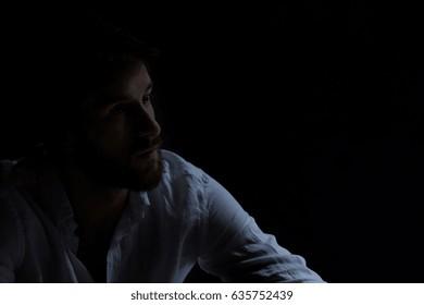 Alone man at room interior stearing at darkness