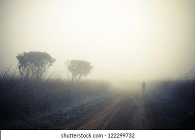 Alone man walking in a fog.