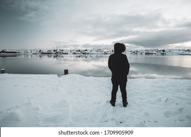 Alone man wearing a coat with hoody on the head and  from his behind walking on snow in Reine, Norway. Snowcapped mountains and  snowcapped ground. Alone man alone standing in front of the sea view.