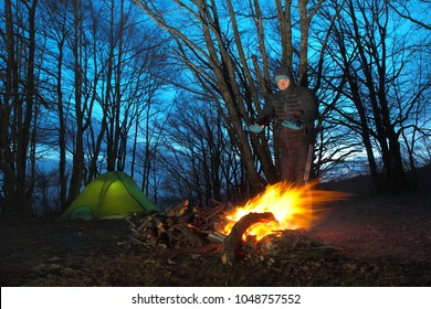 alone man in the wild camp heats his hands on fire at dusk in Nebrodi Park, Sicily