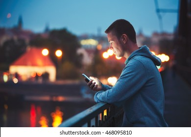 Alone in the night city with mobile phone. Handsome dreamy man reading message (or looking on the video) on his smartphone.