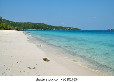 Alone on the private island with white sandy beach, clear blue water, blue sky on a hot summer day at Samaesarn, Sattaheep, Thailand.