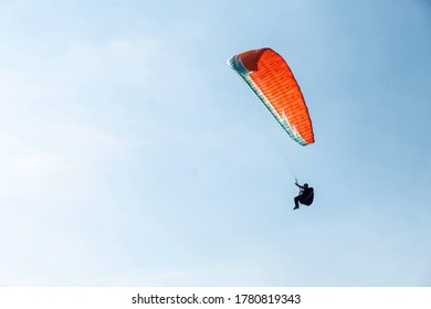 Alone paraglider flying in the blue sky against the background of clouds. Paragliding in the sky on a sunny day.