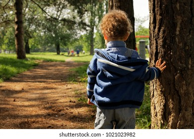 Alone and sad little boy standing in the park, waitng his parent