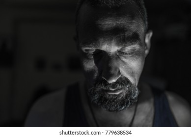 Alone sad man with depression sitting in the darkness.Alone man at room interior stearing at darkness.Depressed and thoughtful man sitting alone in dark room.