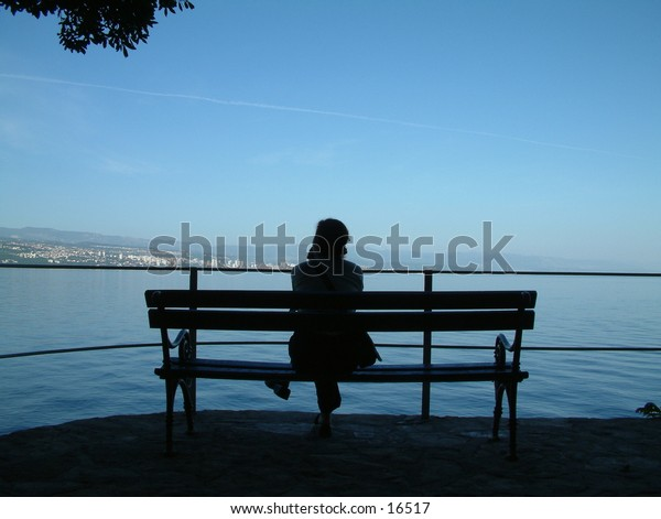 alone in the shadow on the bench near the adriatic sea
