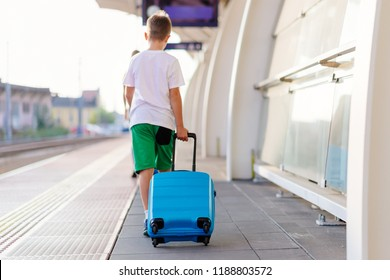 Alone ten years old child with blue baggage on airport or train station.