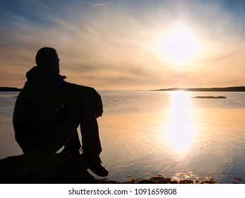 Alone tourist man sitting on a rocky lakeshore and thinking. Relaxing at  a beautiful multicolor sunset above free ocean