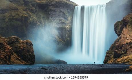 Alone tourist overlooking waterfall at Skogafoss, Iceland