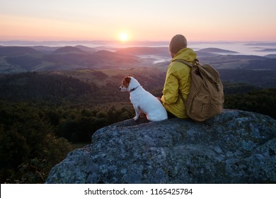 Alone tourist sitting on the edge of the cliff with dog against the backdrop of an incredible mountain landscape. Sunny day and blue sky