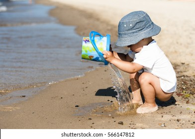 Alone, without care, half naked, one and a half year-old child with sun hat on head, squatting at the sea shore at sunny summer day and playing a bucket of water. Baby at the sea background. Naturist