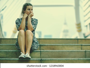 alone woman and depressed sitting on stair walkway of downtown with The pale sky lonely scene, waiting for hope,sad mood,feel tired and unhappy. copy space