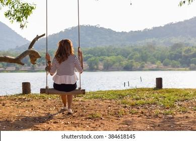 Alone woman sit on swing feel sad in park
