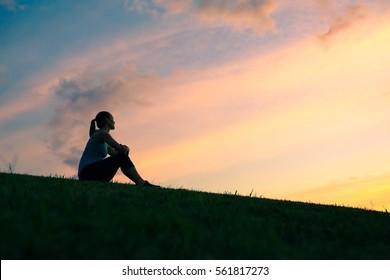 Alone woman sitting watching the sunset/sunrise.