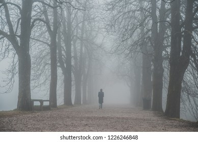 Alone woman walking in misty alley. Depression and loneliness concept photo