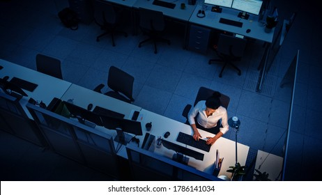 Alone Working Late at Night in the Office: Businesswoman Using Desktop Computer, Analyzing, Using Documents, Solving Problems, Finishing Project. High Angle Shot