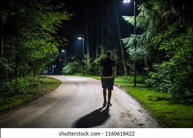 alone young man walking on the night forest road with street lights