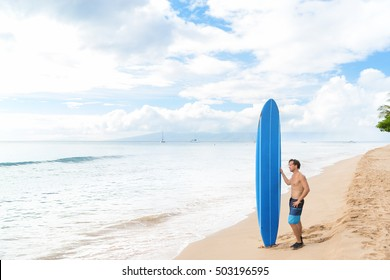 Alone young surfer relaxing looking out to ocean waiting for surfing waves at hawaiian Kaanapali beach in Maui, Hawaii, USA standing with blue longboard surf board. Active man lifestyle.