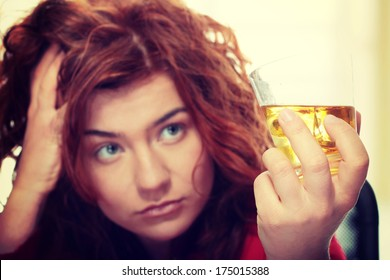 Alone young woman in depression, drinking alcohol (burbon)