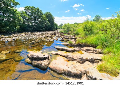 Along the banks of the rock strewn River Ribble near Stainforth on a bright summer day