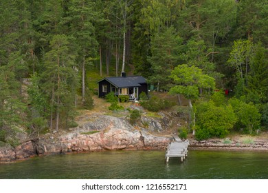 Along house on the Swedish archipelago with own pier. Summer house surrounded with beautiful green nature, water and sky. Traditional Swedish archipelago island and typical red houses