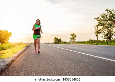Along the road in the hillside area at the time of the sun set woman is exercising by running.