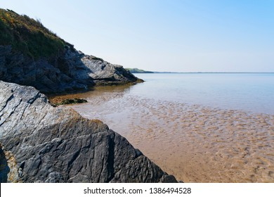 Along the shoreline of the River Dwyryd estuary erroded slate cliffs reach down to wet rippled sand left by a receding tide.