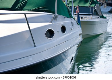 Along the side of a medium sized yacht, with a smaller boat behind, water reflecting in the hull.