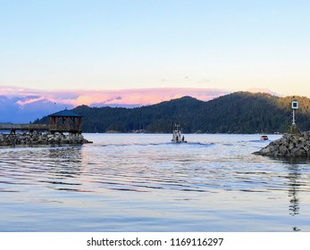 along the Sunshine Coast. Water is calm and tranquil., Boats leaving the harbour as the sun goes down in Gibsons, british columbia