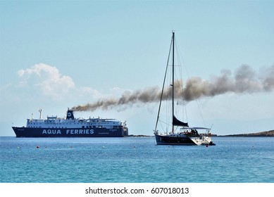 Alonissos, Greece - June 28, 2016: Cruise ferry ship on sea with big black smoke streak line from its chimneys, in contrast to a small fishing boat.
