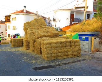 Alora, Spain - August 5, 2018: Council workers preparing to line village street with straw bales ready for soapbox car race