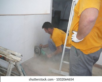 Alora, Spain - December 1, 2011: Man using angle grinder to make room for steel staircase