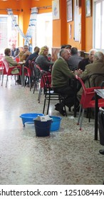 Alora, Spain - November 16, 2018: People enjoying breakfast in bar while buckets catch rainwater from dripping ceiling
